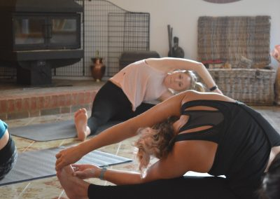 Instructor in the background with retreat attendee in the foreground. Both sat on the floor with legs out stretched and bending to the side for a stretch.